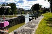 Canal lock gates with touristic boat waiting in France poster