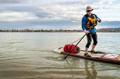 senior man on expedition stand up paddleboard with a large waterprood duffel on deck, a lake in Colo poster