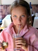 Girl Drinking Chocolate Milk In A Restaurant
