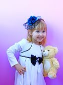 Little Girl In Fashionable Hat And With Toy Bear Cub In Hands Smiling And Posing On Lilac Background poster