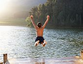 picture of daring  - Young boy jumping into lake - JPG