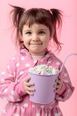 Portrait Of A Cute Little Girl Holding Small Violet Bucket Of Marshmallow, Isolated Over Pink Backgr poster