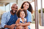 Young black family embracing outdoors and smiling at camera poster