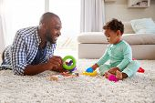 Black dad and toddler son playing on floor at home, close up poster