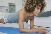 Young ethnic model in sportswear looking forward with concentration while training abdominal muscles poster