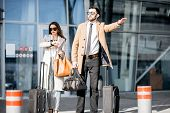 Business Couple Catching A Taxi Standing With Luggage Near The Airport poster
