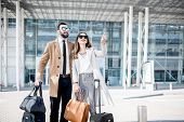 Business Couple In Coats Standing Near The Airport With Luggage During The Business Trip poster
