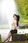 stock photo of waterspout  - A smiling beautiful brunette woman with a cowboy hat in her twenties sitting next to a pond with a fountain in the background - JPG