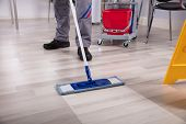 Cleaner Cleaning Hardwood Floor With Mop At Workplace poster