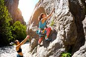 Two Girls Are Trained In Natural Relief. Rock Climber Climbs A Rock. Woman Insures A Friend. Mountai poster