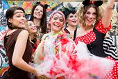 Group of cheerful women in sexy costumes at carnival party poster