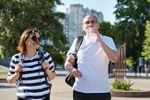 Mature Smiling Man And Woman In Sportswear With Backpacks Exercise Mat Walking In City Park Talking  poster