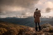A Woman In A Brown Coat With Fur Collar Standing On A Hilltop In Corsica And Enjoying The View Of Th poster