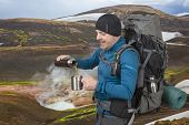 Happy Tourist Man Pours Hot Tea From A Thermos On A Background Of Mountainous Terrain. Beautiful And poster