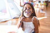Adorable toddler playing around lots of toys at kindergarten poster