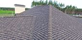 House With A Roof From A Bituminous Tile. Bituminous Tile For A Roof. A Roof From A Bituminous Tile. poster