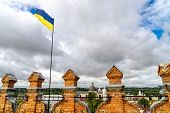 View Of Lubart Castle Tower In Lutsk In Ukraine With Ukrainian Flag On Sunny Summer Day. The Top Of  poster