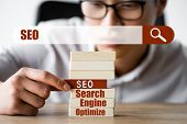 Selective Focus Of Asian Seo Manager Holding Wooden Rectangle With Lettering Seo And Sitting Near Se poster