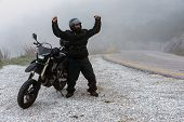 Rider Celebrate His Successful Ride On A Foggy Day In The Mountains poster