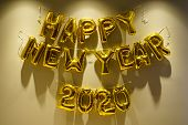 Celebrating The New Year 2020. Gold Foil Balloons On A Yellow Background. Foil Balls, Festive Concep poster