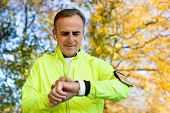 Mature Man Exercising In Autumn Woodland Looking At Activity Tracker On Smart Watch poster