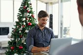 Happy young businessman working on laptop during christmas holiday. Successful business man in moder poster