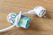 Electric Cable With Plug Tied To A Knot On A Roll Of Euro Banknotes. Cost Of Electricity And Expensi poster