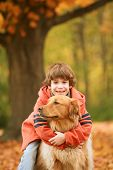 image of fall leaves  - Boy Hugging the Dog in the Fall - JPG
