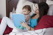 pic of babysitter  - Young mother reading a story to her baby girl before going to bed - JPG
