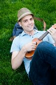 stock photo of ukulele  - happy young male student on campus with ukulele - JPG