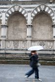 Santa Maria Novella Church; Florence; Italy With Couple Walking With Umbrellas