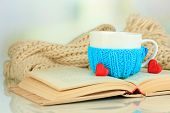 stock photo of hot-weather  - Cup with knitted thing on it and open book close up - JPG