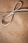 String tied in a bow, over brown package paper