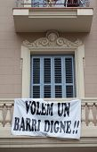 Protest banner hanging off the balustrade on a building facade saying Volem Un Barri Digne, or We Wa