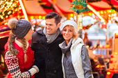 stock photo of merry-go-round  - Man and women or friends during advent season or holiday in front of a carousel or merry - JPG