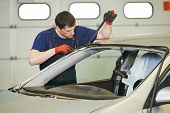Automobile glazier worker disassembling windscreen or windshield of a car in auto service station ga