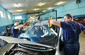 Automobile glaziers workers replacing windscreen or windshield of a car in auto service station gara