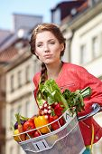 Pretty spring  woman with bicycle and groceries in old town street.