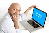picture of terrifying  - latin worried businessman biting finger nails in anxiety working on computer in system error - JPG