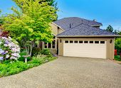 picture of driveway  - House exterior. View of garage with driveway and beautiful green flower bed ** Note: Soft Focus at 100%, best at smaller sizes - JPG