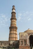 stock photo of qutub minar  - Qutub minar view from southern direction and leading entry from the side gate.