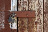 foto of hasp  - padlocked hasp on weathered painted brown wood door - JPG