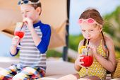 stock photo of cabana  - Kids at luxury resort relaxing at beach cabana and drinking tropical juices - JPG