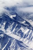 image of snow capped mountains  - Top view on snow mountains and glacier in fog - JPG