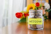 pic of coins  - Many world coins in a money jar with wedding label on jar beautiful flowers on background - JPG