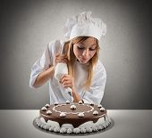 stock photo of confectioners  - Pastry cook prepares a cake with cream and chocolate - JPG