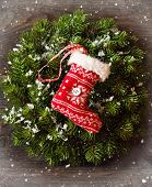 foto of christmas wreath  - Christmas decoration with Christmas wreath and hanging stocking on snow wooden board - JPG