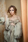 stock photo of provocative  - Attractive sexy young woman wearing a fur coat posing provocatively indoor - JPG