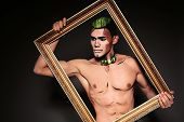 stock photo of beast-man  - fashion studio photo of sexy muscular man with painted face and chest for Halloween party - JPG