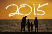 stock photo of children beach  - Silhouette of happy family playing on beach and enjoy new year holiday of 2015 - JPG